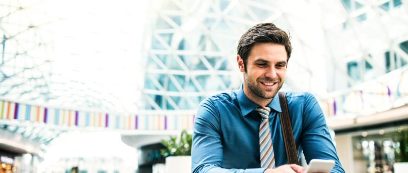 A young businessman with smartphone standing in a modern building, text messaging.